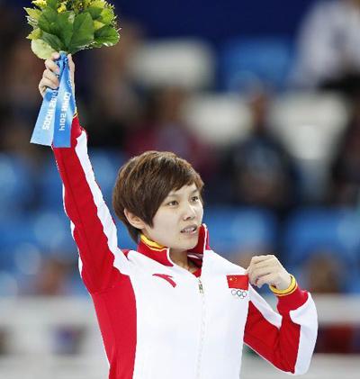 中国选手李坚柔在献花仪式上手摸国旗庆祝胜利。新华社发