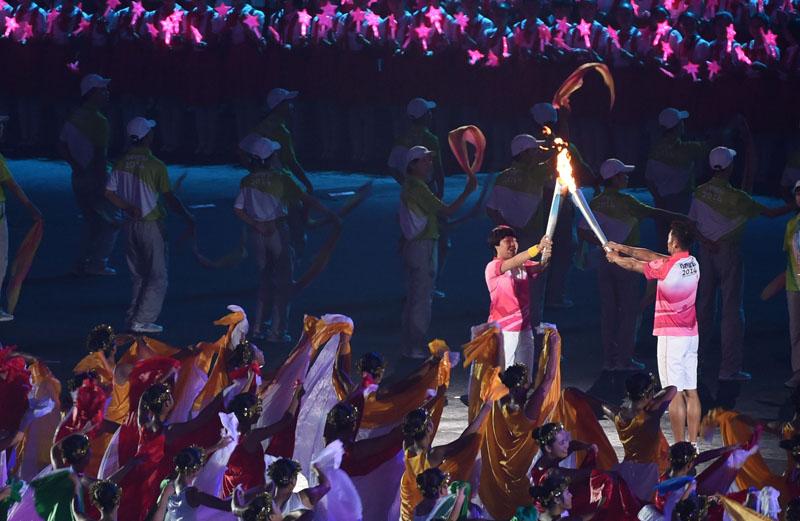 开幕式上火炬手、著名羽毛球运动员林丹(右)与火炬手、著名短道速滑运动员周洋交接火炬。新华社记者燕雁摄